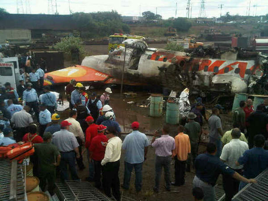 In this image courtesy of Globovision Television News, people surrounds  the wreckage of an airplane of a state airline Conviasa after it crashed about 6 miles (10 kilometers) from the eastern city of Puerto Ordaz, Venezuela, Monday, Sept. 13, 2010.  The plane was carrying 51 people, and officials said at least 21 people survived.(AP Photo/Globovison) Photo: ASSOCIATED PRESS / GLOBOVISION