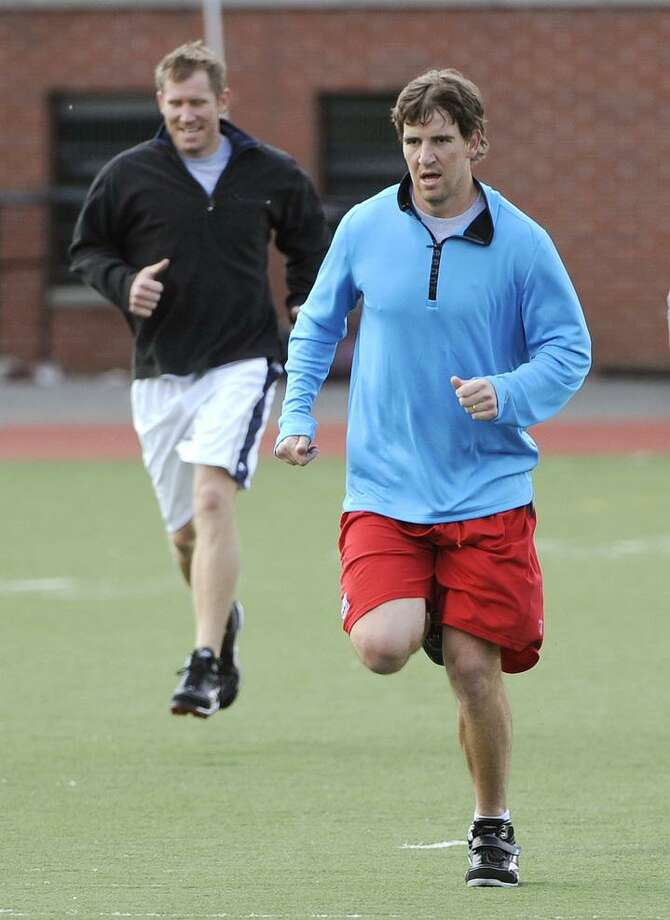 New York Giants quarterbacks Eli Manning, right, and Sage Rosenfels run during a football workout for Giants players hosted by Manning at Hoboken High School, Thursday, May 5, 2011, in Hoboken, N.J. The workout gives the players an opportunity to practice together during the NFL labor lockout. (AP Photo/Bill Kostroun) Photo: ASSOCIATED PRESS / AP2011