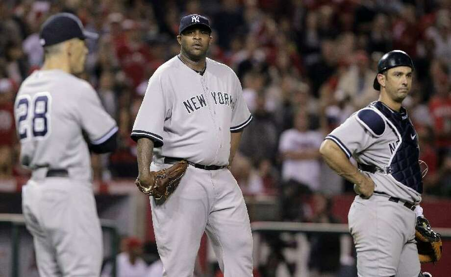 ASSOCIATED PRESS New York Yankees starting pitcher CC Sabathia, center, manager Joe Girardi, left, and catcher Jorge Posada watch as umpires confer in the sixth inning of Saturday's game against the Los Angeles Angels in Anaheim, Calif. The Yankees lost 6-0.