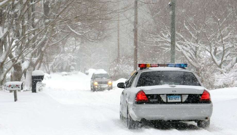 The snowstorm in the Ivoryton section of Essex. A state trooper slowly approaches a car parked and running on the wrong side of the road. Photo by Mara Lavitt/New Haven Register1/12/11