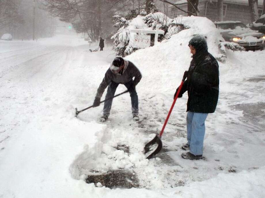 Ronald Angiollo and April Amore clean their driveway along Short Beach Rd in Branford early Wednesday morning as snow continued to fall after already accumlulating more than a foot overnight. VM Williams 01.12.11