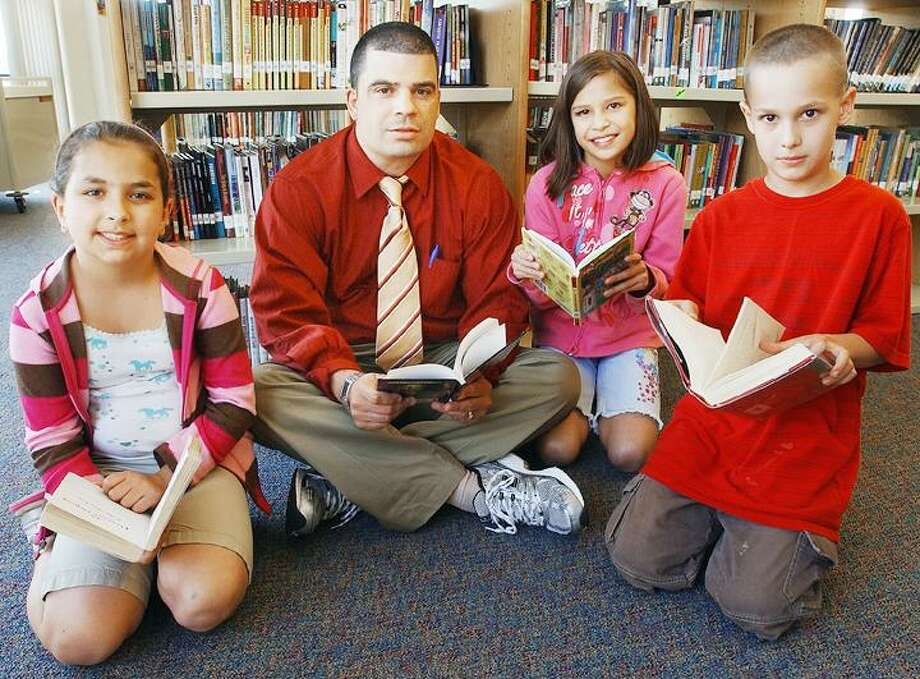 """Principal Bo Ryan sits with third-grader Carina Fortunato, 9, fourth-grader Angelina Olsen, 9, and third-grader Alex Liseo, 9, in the library at Woodside Intermediate School in Cromwell. Mr. Ryan's Reading Program, which meets before and after school, is believed to be the reason why mastery scores improved. Fortunato, Olsen and Liseo had perfect attendance in the program. To buy a glossy print of this photo and more, visit <a href=""""http://www.middletownpress.com"""">www.middletownpress.com</a>. (Catherine Avalone"""