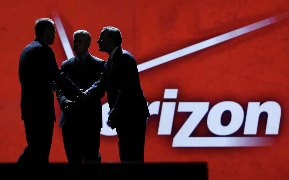 Consumer Electronics Association president and Chief Executive Officer Gary Shapiro, left, greets Verizon Communications Inc., chairman and Chief Executive Officer Ivan Seidenberg, right, and president and Chief Operating Officer Lowell McAdam during the Consumer Electronics Show, in Las Vegas. As the tech industry awaits a likely Verizon iPhone announcement on Tuesday. Shares of Apple Inc. hit a record high during Monday trading.  (AP Photo/Julie Jacobson, file) Photo: ASSOCIATED PRESS / AP2011