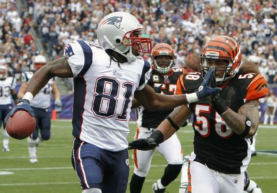 New England Patriots wide receiver Randy Moss (81) fends off Cincinnati Bengals linebacker Rey Maualuga (58) in the second quarter of an NFL football game Sunday in Foxborough, Mass. (AP Photo/Michael Dwyer) Photo: AP / AP