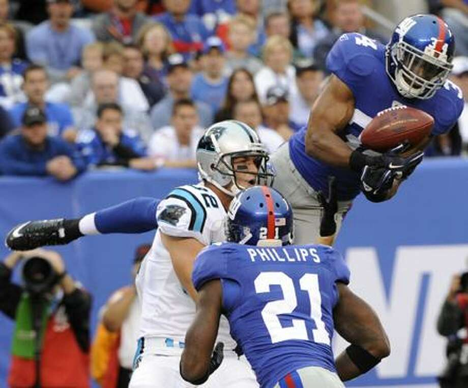 New York Giants safety Deon Grant (34) intercepts a pass as teammate Kenny Phillips (21) and Carolina Panthers tight end Gary Barnidge (82) look on during an NFL football game at New Meadowlands Stadium in East Rutherford, N.J., Sunday. (AP Photo/Bill Kostroun) Photo: AP / FR51951 AP