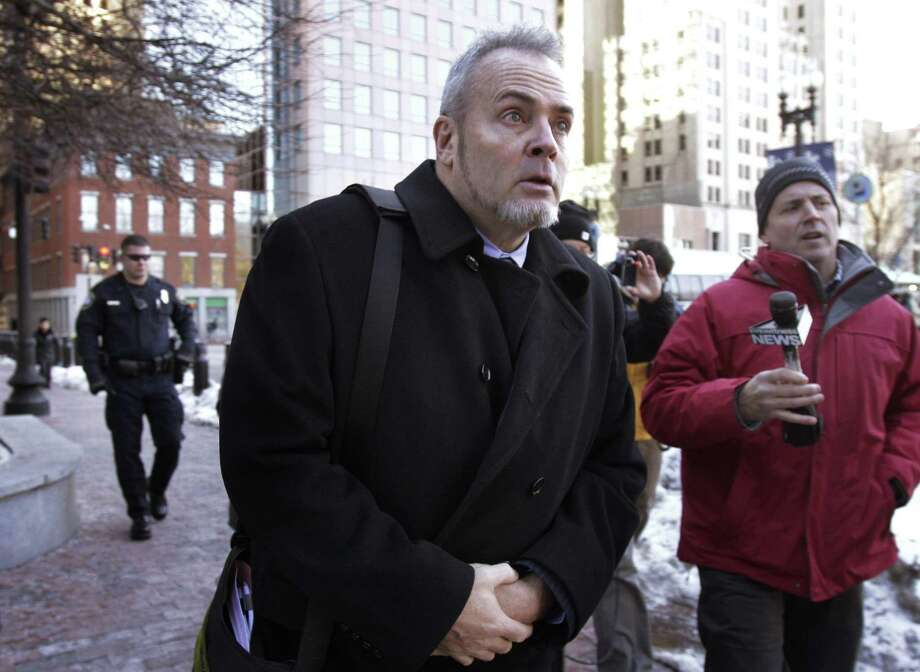 """Reality TV star Richard Hatch, center, departs federal court in Providence, R.I., Monday. In 2009 Hatch began a three-year period of supervised release under the condition that he refile and pay his taxes on the """"Survivor"""" winnings and other income. The court found Monday that he violated the terms of his supervised released. (AP Photo/Steven Senne) Photo: AP / AP"""