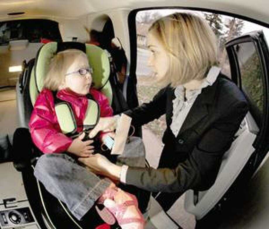 (AP) In this Dec. 18 photo, Anne Epperson unbuckles her daughter Madeline, 3, from her car seat at their home in Westwood, Kan. Many parents find themselves confused by new car seat research that suggests children should remain in rear-facing car seats much longer than the one year of age or 20 pound benchmark long accepted by officials Photo: ASSOCIATED PRESS / AP2009