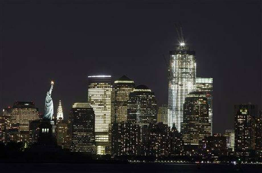 In this Aug. 23, 2011 file photo, One World Trade Center rises above the Manhattan skyline and the Statue of Liberty, in New York. The tower will be 104 floors and 1,776 feet (541 meters) tall when completed. Ten years after terrorists destroyed the World Trade Center, the new World Trade Center is rising from ground zero. (AP Photo/Mark Lennihan, File) Photo: AP / AP2011