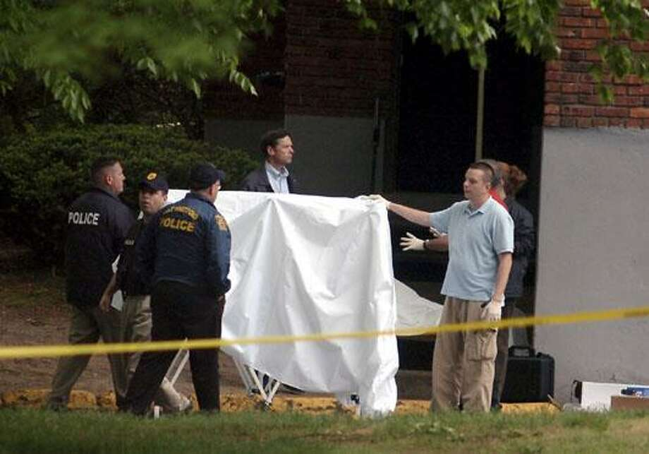 Police investigate the scene at an East Hartford, Conn., apartment complex where three people have been killed and another wounded in a mid-morning shooting, Thursday, May 6, 2010.  Police say two males and one female were found dead in a third-floor apartment Thursday morning. The fourth victim was taken to a hospital..  (AP Photo/Journal Inquirer, Leslloyd F. Alleyne) MANDATORY CREDIT Photo: AP / AP2010