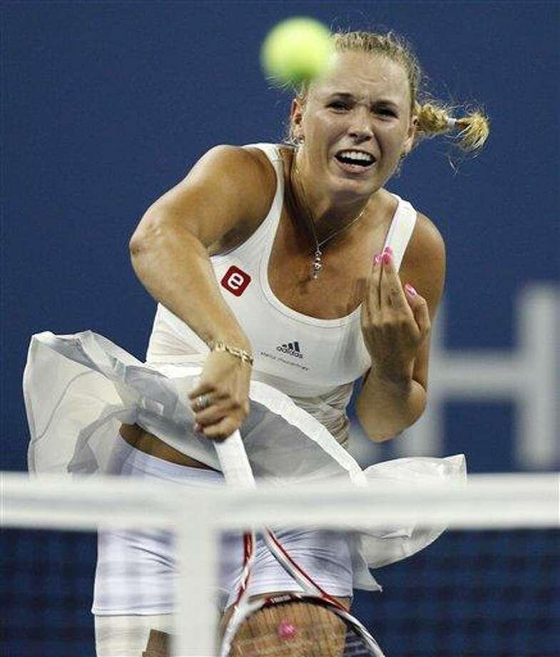 Caroline Wozniacki, of Denmark, smashes a shot at the net against Svetlana Kuznetsova, of Russia, during the U.S. Open tennis tournament, Monday, Sept. 5, 2011, in New York. Woznizcki won 6-7 (6), 7-5, 6-1. (AP Photo/Charles Krupa) Photo: AP / AP