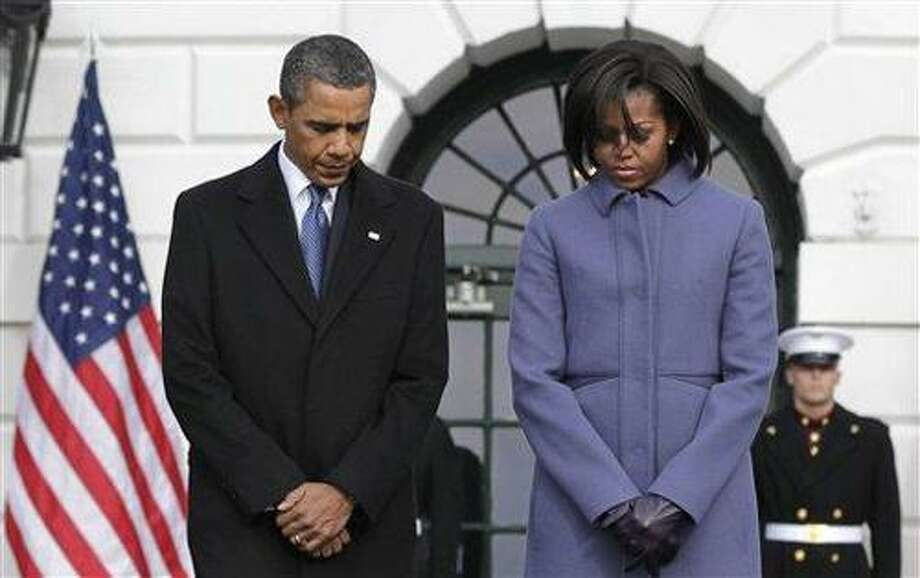President Barack Obama and first lady Michelle Obama are joined by government employees on the South Lawn of the White House in Washington, Monday, Jan. 10, 2011, to observe a moment of silence for Rep. Gabrielle Giffords, D-Ariz., and the other victims of an assassination attempt against her. The shooting at a town hall-style event outside a supermarket in Tucson, Ariz., Saturday left six dead, including a federal judge, and critically wounded Rep. Gabrielle Giffords. (AP Photo/J. Scott Applewhite) Photo: ASSOCIATED PRESS / AP2011