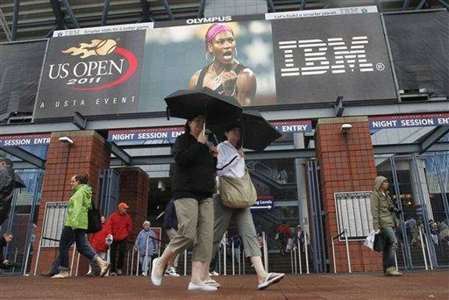 Fans walk near an entrance to Arthur Ashe Stadium during the U.S. Open tennis tournament in New York, Tuesday, Sept. 6, 2011. The U.S. Tennis Association announced just after 1:30 p.m. that because of unfavorable forecasts, it would have to cancel both the day and night sessions, hoping to resume play at 11 a.m. Wednesday, Sept. 7, 2011. (AP Photo/Mike Groll) Photo: AP / AP