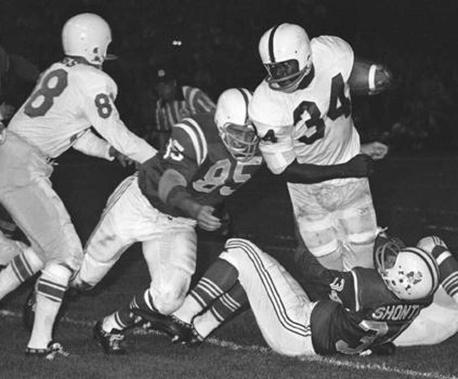 FILE - In this September 1962 file photo, Buffalo Bills fullback Cookie Gilchrist (34) is brought down by Boston Patriots' Chuck Shonta (34) during an exhibition football game in Boston. Boston's Nick Buoniconti (85) and Bills' Mack Yoho (81) are at left. Former American Football League star Gilchrist has died of cancer at 75. Nephew Thomas Gilchrist says his uncle died Monday, Jan. 10, 2011, at an assisted living facility near Pittsburgh. Gilchrist spent three seasons in Buffalo, two in Denver and one in Miami. (AP Photo/Bill Chaplis, File) Photo: AP / AP1962