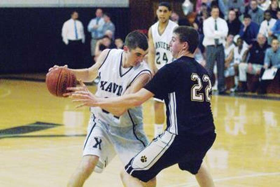 Xavier's Tucker Landy keeps the ball away from Hand's Riley Kirsch Monday night at Xavier high school in Middletown. Xavier lost in the SCC quarterfinals Thursday to Hamden, 58-54. (Max Steinmetz / Special to the Press)