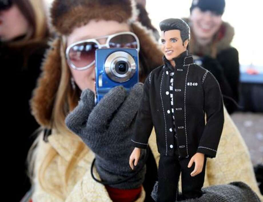 """Julia Rose, 37, of Fort Worth, Texas, brought her own """"mini king"""" as she makes photos of the cake at a party celebrating Elvis Presley's birthday and the proclamation of Elvis Presley Day on the front lawn of Graceland in Memphis, Tenn., Saturday, Jan. 8, 2011. (AP Photo/The Commercial Appeal, Mike Maple) NO SALES, MAGS OUT, TV OUT, ONLINE OUT, MEMPHIS OUT Photo: ASSOCIATED PRESS / AP2011"""