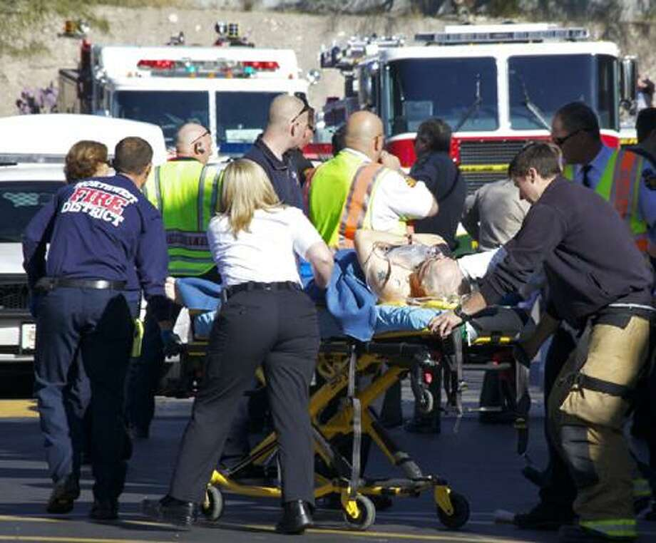 Emergency personnel attend to a shooting victim  outside a shopping center in Tucson, Ariz. on Saturday, Jan. 8, 2011 where U.S. Rep. Gabrielle Giffords, D-Ariz., and others were shot as the congresswoman was meeting with constituents.  (AP Photo/James Palka) Photo: ASSOCIATED PRESS / AP2011