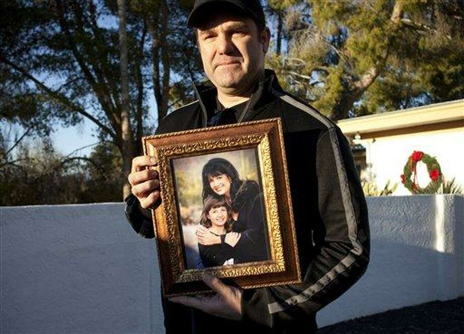 Greg Segalini holds a photo of his niece Christina Green and his sister, Roxanna Green Saturday Jan. 8, 2011. Segalini, an uncle of Christina, the 9-year-old victim of the shooting spree by Jared Loughner Saturday, told the Arizona Republic that a neighbor was going to the event and invited her along because she had just been elected to the student council and was interested in government. (AP Photo/Mark Henle - The Arizona Republic) Photo: AP / The Arizona Republic
