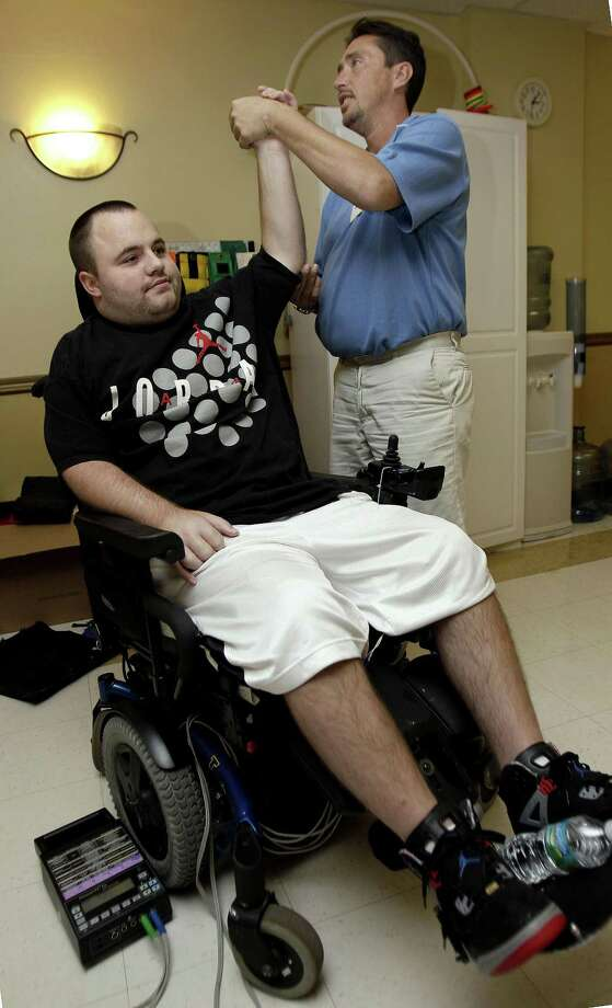 In this photo quadriplegic Adam Martin, left, works with physical therapist Wes Bower at the Sarasota Health and Rehabilitation Center. It's no longer unusual to find a nursing home resident who is decades younger than his neighbor: About one in seven people now living in such facilities in the U.S. is under 65. (AP Photo/Chris O'Meara) Photo: ASSOCIATED PRESS / AP2010