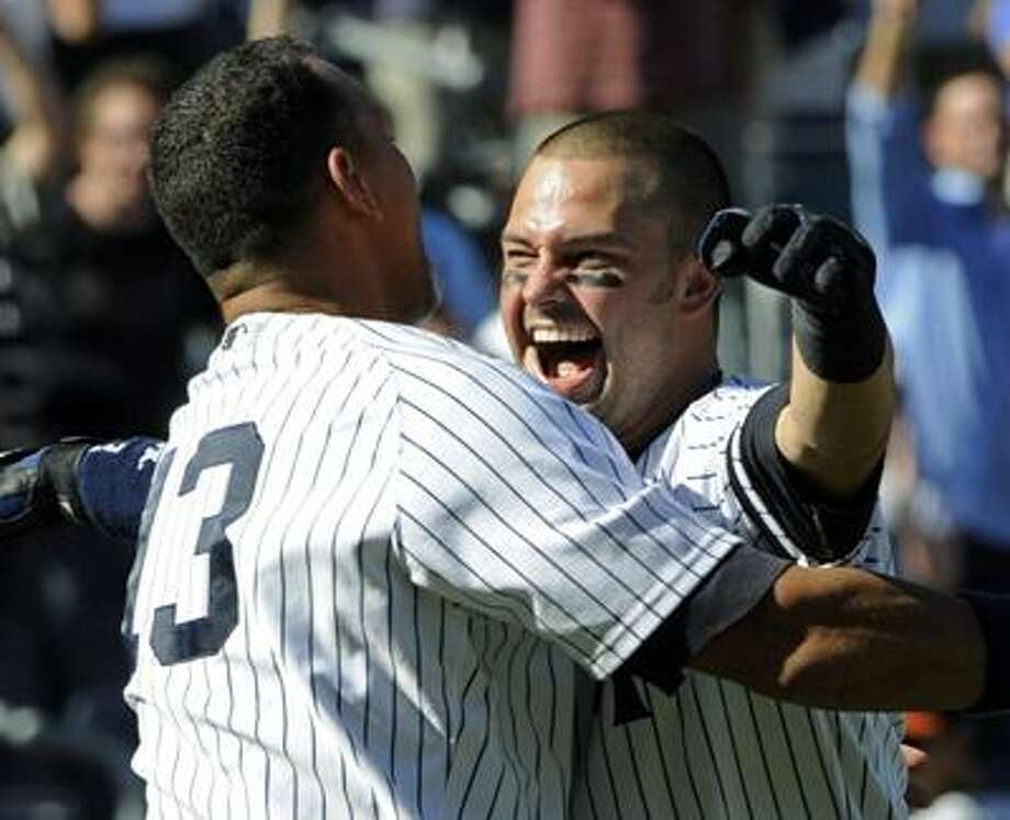 New York Yankees' Nick Swisher, right, is hugged by Alex Rodriguez after Swisher hit the game-winning two-run walk-off home run in the ninth inning to beat the Baltimore Orioles 3-2 in a baseball game Wednesday. (AP) Photo: ASSOCIATED PRESS / FR51951 AP