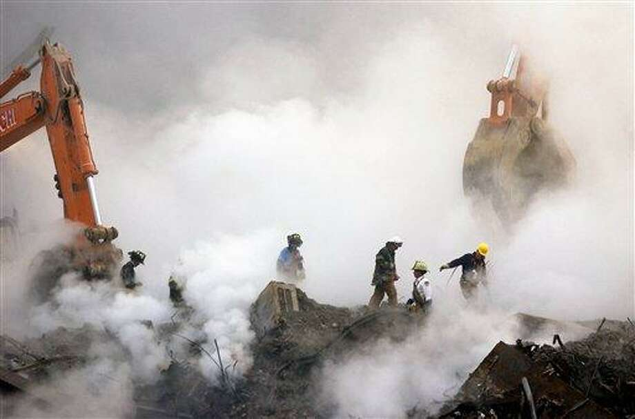 FILE - In this Oct. 11, 2001 file photo, firefighters make their way over the ruins of the World Trade Center through clouds of smoke at ground zero in New York. A decade's worth of study has answered only a handful of questions about the hundreds of health conditions believed to be related to the tons of gray dust that fell on the city when the trade center collapsed, from post-traumatic stress disorder, asthma and respiratory illness to vitamin deficiencies, strange rashes and cancer. .(AP Photo/Stan Honda, Pool) Photo: AP / POOL AFP