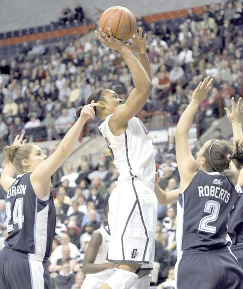 Connecticut's Maya Moore takes a one-hander goes up for a shot as Villanova's Megan Pearson, left, and Rachel Roberts, right, defend during the first half of an NCAA college basketball game in Storrs, Conn., Wednesday, Jan. 5, 2011. (AP Photo/Bob Child) Photo: AP / FR170410 AP
