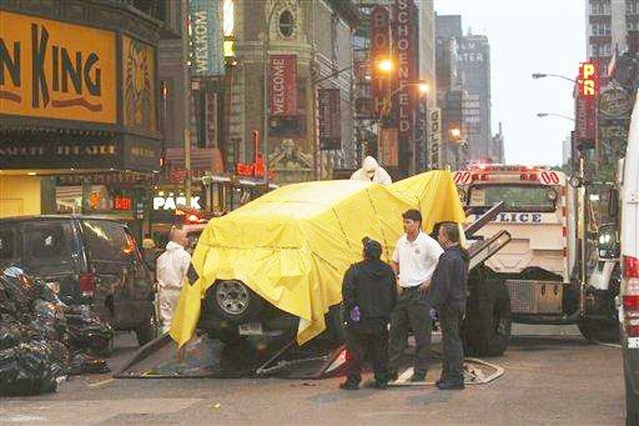 """(AP) Police tow a vehicle from New York's Times Square early Sunday, after an """"amateurish"""" but potentially powerful bomb was found inside it on Saturday evening. Thousands of tourists were cleared from the streets for 10 hours after two vendors alerted police to the suspicious vehicle, which contained three propane tanks, fireworks, two filled 5-gallon gasoline containers, and two clocks with batteries, electrical wire and other components, Police Commissioner Raymond Kelly said. Photo: AP / The New York Times"""
