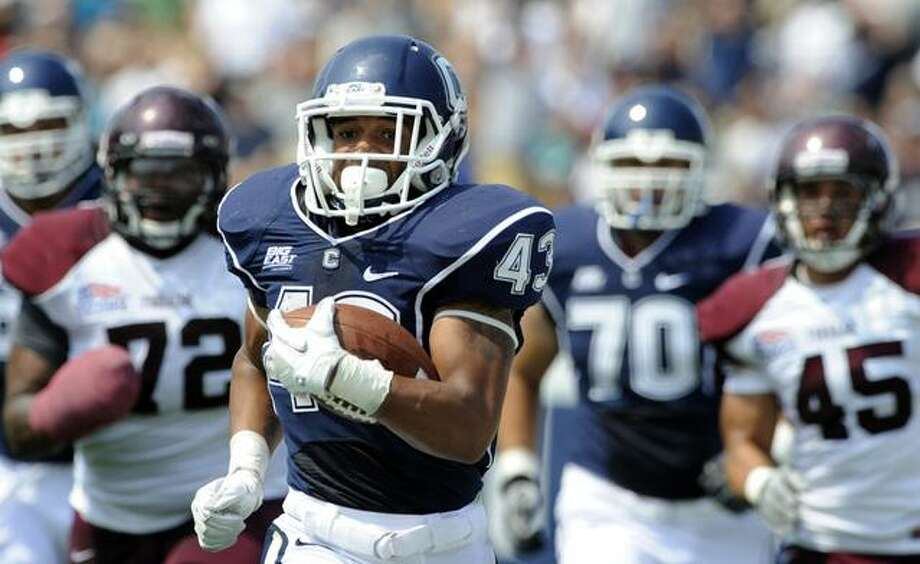 Connecticut's Lyle McCombs is pursued by Fordham's Justin Yancey (72) and Jake Rodriques (45) while making a 60-yard run during the first half of an NCAA college football game in East Hartford, Conn., on Saturday, Sept. 3, 2011. (AP Photo/Fred Beckham) Photo: ASSOCIATED PRESS / AP2011