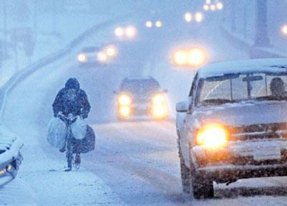 """Herbie J. Zampano, 61, of Branford, known as """"The Bikeman,"""" pedaled his bike through the snow on Saltonstall Parkway in East Haven Friday on his way to Forbes Avenue in New Haven.  Zampano says he rides his bicycle 45 miles a day through all kinds of weather, collecting recyclable cans and bottles and scrap metal along the way. He usually has a cart attached to the bike, but went without it Friday. (Peter Hvizdak/Register)"""