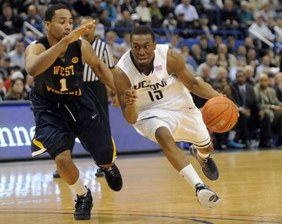 Connecticut's Kemba Walker drives past West Virginia's Da'Sean Butler in the second half of Connecticut's 73-62 victory Monday. (Associated Press) Photo: ASSOCIATED PRESS / AP2010