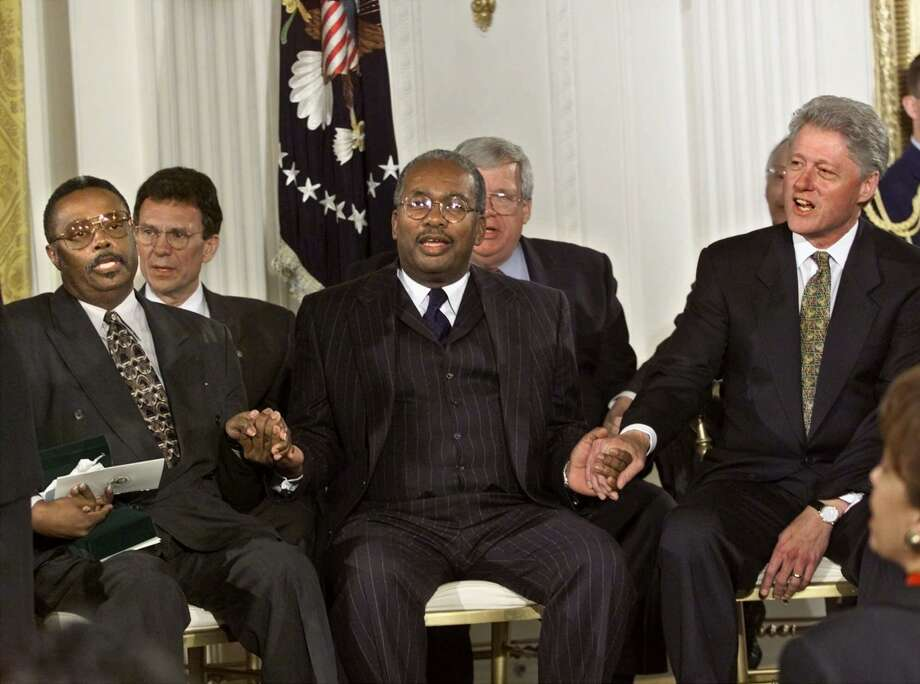 In a Nov. 9, 1999 file photo, President Clinton sings with Jefferson Thomas, far left, and Ernest Green, center, at the conclusion of a Congressional Gold Medal ceremony in the White House, to honor them and the other members of The Little Rock Nine. (AP Photo/J. Scott Applewhite) Photo: ASSOCIATED PRESS / AP
