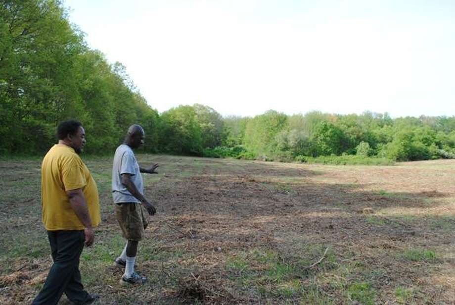Larry Owens and Robert James Jr. of Middletown United Fathers walk through the multi-acre plot of land Common Council leased to them Wednesday for use as a community garden.