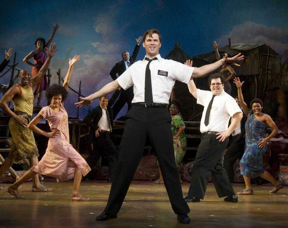 "In this theater publicity image released by Boneau/Bryan-Brown, Andrew Rannells, center, performs with an ensemble cast in ""The Book of Mormon"" at the Eugene O'Neill Theatre in New York. ""The Book of Mormon"" nabbed a leading 14 Tony Award nominations Tuesday morning, earning the profane musical nods for best musical, best book of a musical, best original score, two leading actor spots and two featured actor nominations.  (AP Photo/Boneau/Bryan-Brown, Joan Marcus) Photo: AP / AP2011"