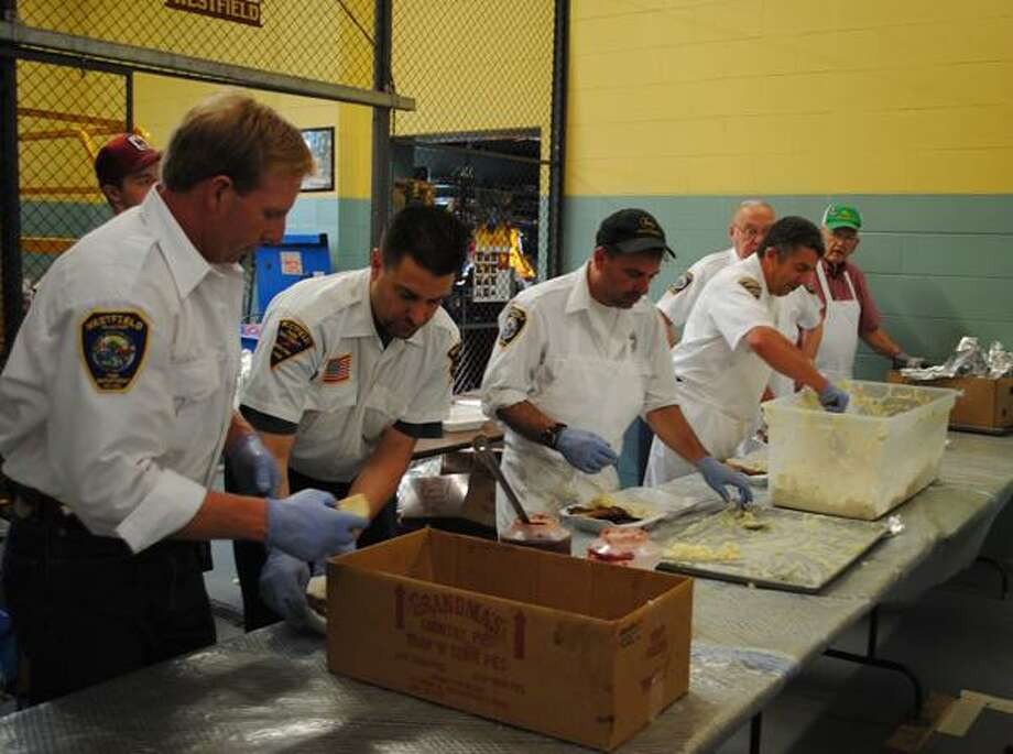 Members of the Westfield Fire Department pack take-home dinners during the department's annual chicken barbecue Saturday.