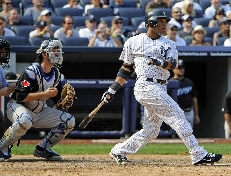 ASSOCIATED PRESS New York Yankees second baseman Robinson Cano follows through on a two-run double as Toronto Blue Jays catcher J.P. Arencibia, left, looks on during the seventh inning of Saturday's game at Yankee Stadium in New York. The Yankees won 6-4.