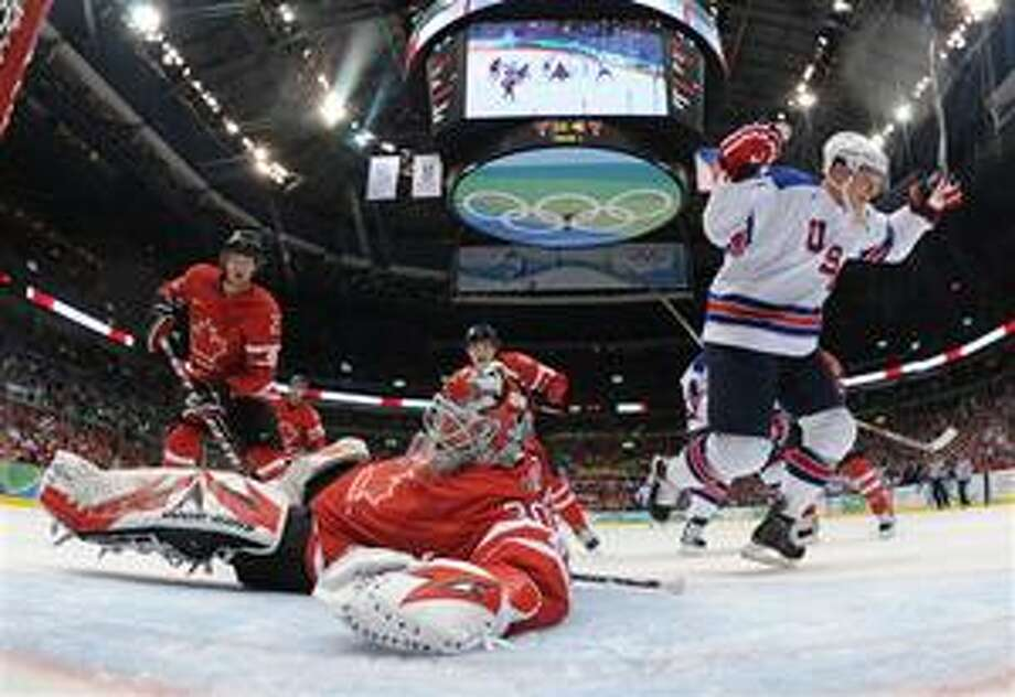 (AP) USA's Jamie Langenbrunner (15) reacts after teammate Brian Rafalski, not shown, scored past Canada's goalie Martin Brodeur (30) in the first period in men's preliminary round hockey play at the Vancouver 2010 Olympics in Vancouver, British Columbia, Sunday. Photo: AP / Getty Pool