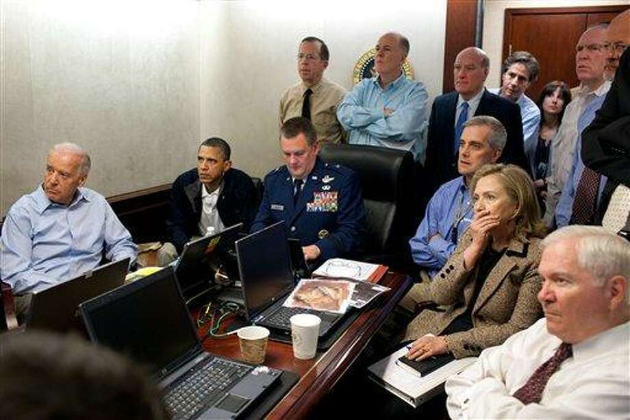 In this image released by the White House and digitally altered by the source to diffuse the paper in front of Secretary of State Hillary Rodham Clinton, President Barack Obama and Vice President Joe Biden, along with with members of the national security team, receive an update on the mission against Osama bin Laden in the Situation Room of the White House, Sunday, May 1, 2011, in Washington. (AP Photo/The White House, Pete Souza) Photo: AP / The White House