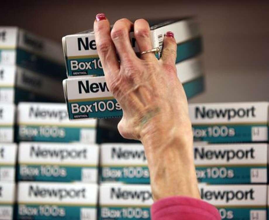 In this Aug. 23, 2010 photo, a customer selects cartons of cigarettes at a smoke shop on the Tonawanda Seneca Nation in New York. (AP Photo/David Duprey) Photo: AP / AP