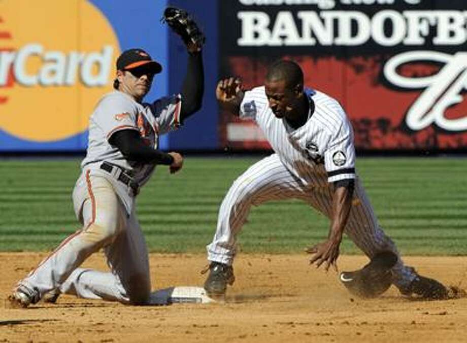 Baltimore Orioles second baseman Brian Roberts, left, looks for the call after tagging out New York Yankees' Greg Golson attempting to steal second base during the seventh inning of a baseball game Monday. (AP) Photo: ASSOCIATED PRESS / FR51951 AP