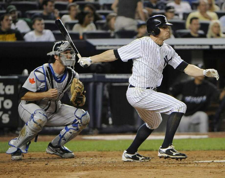 ASSOCIATED PRESS New York Yankees left fielder Brett Gardner follows through on a two-run home run as Toronto Blue Jays catcher J.P. Arenciba, left, looks on during the third inning of Friday's game at Yankee Stadium in New York. The Yankees won 3-2.