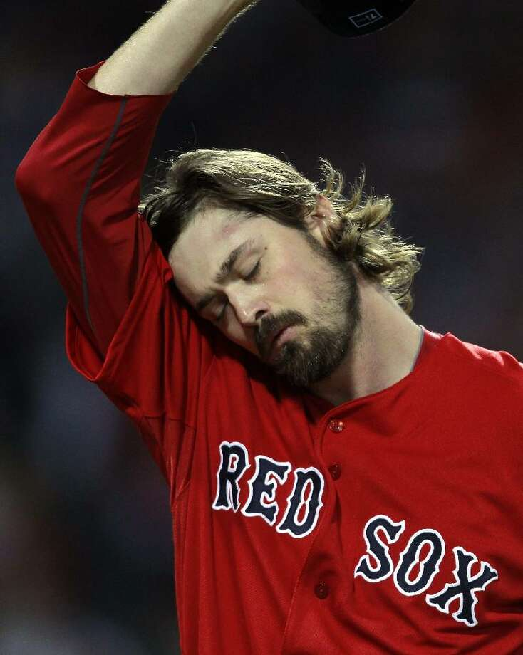 ASSOCIATED PRESS Boston Red Sox starting pitcher Andrew Miller wipes his head as he walks to the dug out after giving up two runs to the Texas Rangers the first inning of Friday's game in Boston.