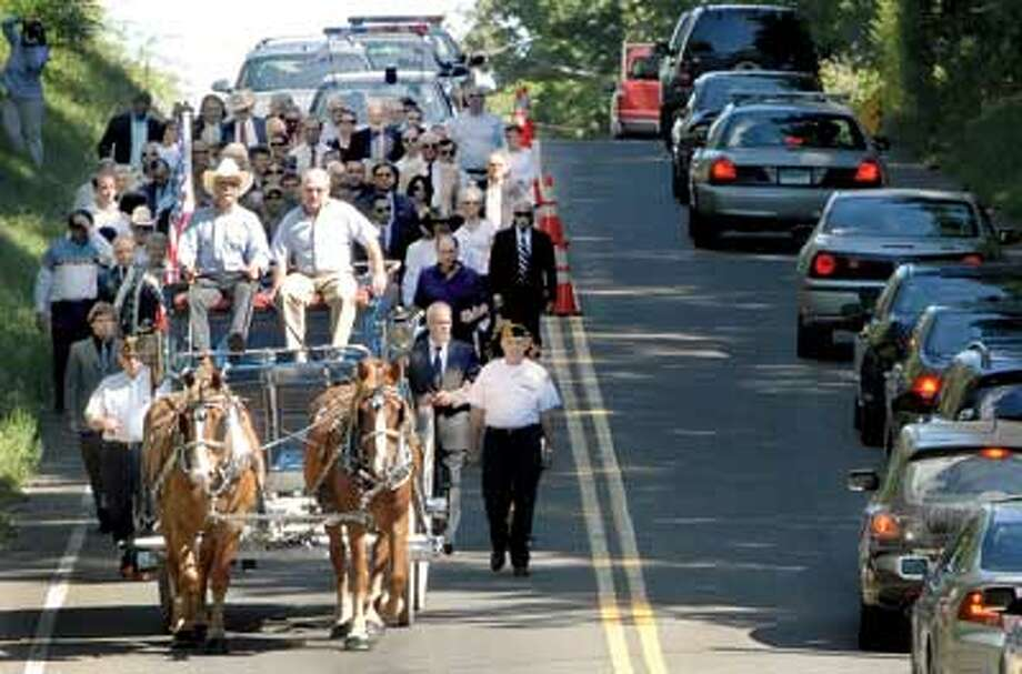 """A horse-drawn carriage takes the body of Bethany's Joseph A. """"U.J."""" Kriz to The First Church Burial Ground Saturday. At the reins is Tim Kriz, Joseph's nephew. In the passenger seat is Glenn Kriz, another nephew. (Peter Hvizdak/Register)"""
