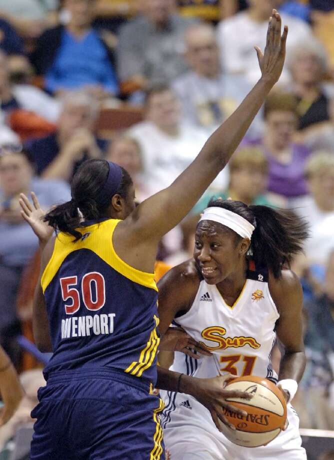 ASSOCIATED PRESS Connecticut Sun's Tina Charles, right, drives to the hoop past Indiana Fever's Jessica Davenport during the first half of Connecticut's 83-55 victory in their game in Uncasville on Friday. Charles had a triple double in the game with 10 points, 10 assists, and 16 rebounds.