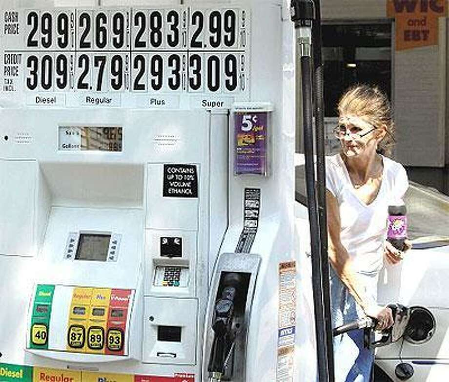 Colleen Carbone of Westbrook fills up her car with gas at Gerry's Shell Food Mart during a visit to her sister's house in New Haven. (Peter Hvizdak/Register)