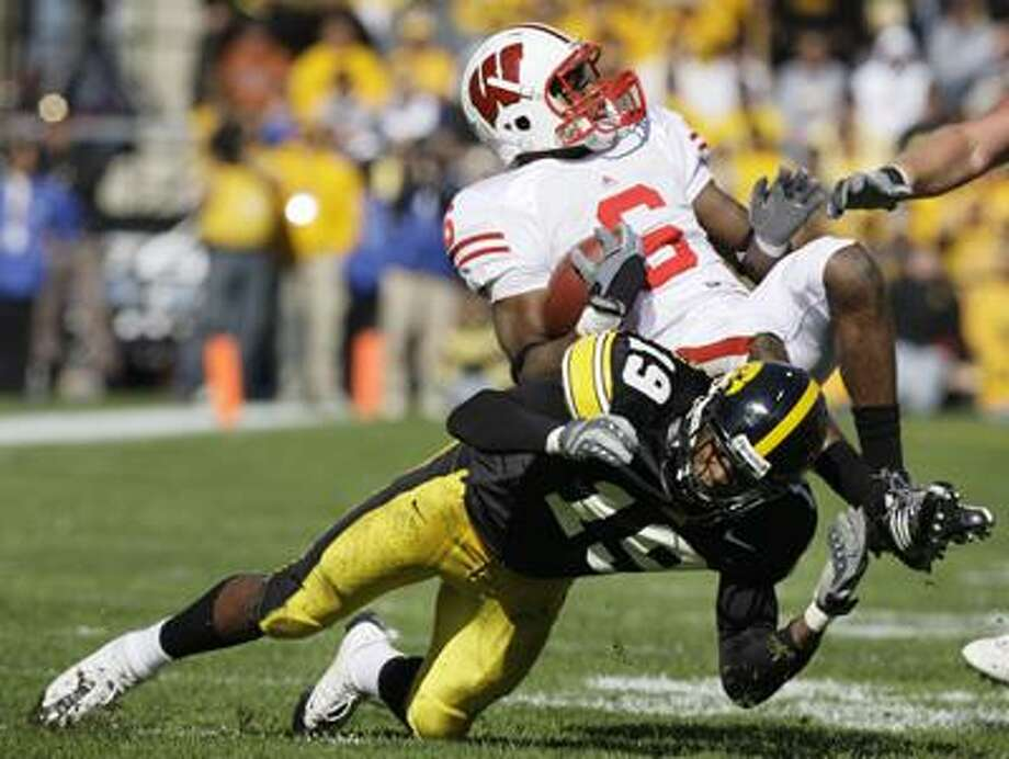 Wisconsin's Isaac Anderson (6) is upended by Iowa's Amari Spievey (19) after catching a pass during the second half of an NCAA college football game, Saturday, Oct. 18, 2008, in Iowa City, Iowa. (AP) Photo: ASSOCIATED PRESS / AP2008