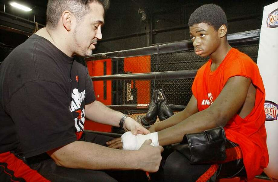 "Hartford resident, Johnny Callas, head coach of the Champions of Life program at the Lions Den in Middletown, wraps the hands of Jerod Gaskins, 16, of Middletown. Gaskins, is the Western New England Novice Middle Weight Golden Glove Champion. Callas said, ""Wrapping or taping of the hands is a ritual between coach and boxer and puts both of us in a meditative state."" (Catherine Avalone / The Middletown Press)"