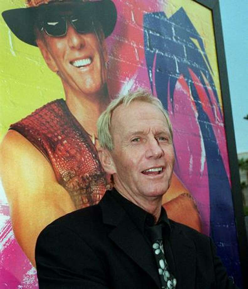 """** FILE ** In this April 18, 2001 file photo, Australian actor Paul Hogan, star of the """"Crocodile Dundee"""" movie trilogy, poses in front of a movie poster for """"Crocodile Dundee in Los Angeles,"""" at a screening of the movie, at the Paramount studios in Los Angeles, Calif. Hogan has been cleared to return home to the United States after he was barred last month from leaving Australia because of a disputed tax bill, his lawyer said Friday, Sept. 3, 2010. (AP Photo/Rene Macura, File) Photo: ASSOCIATED PRESS / AP"""