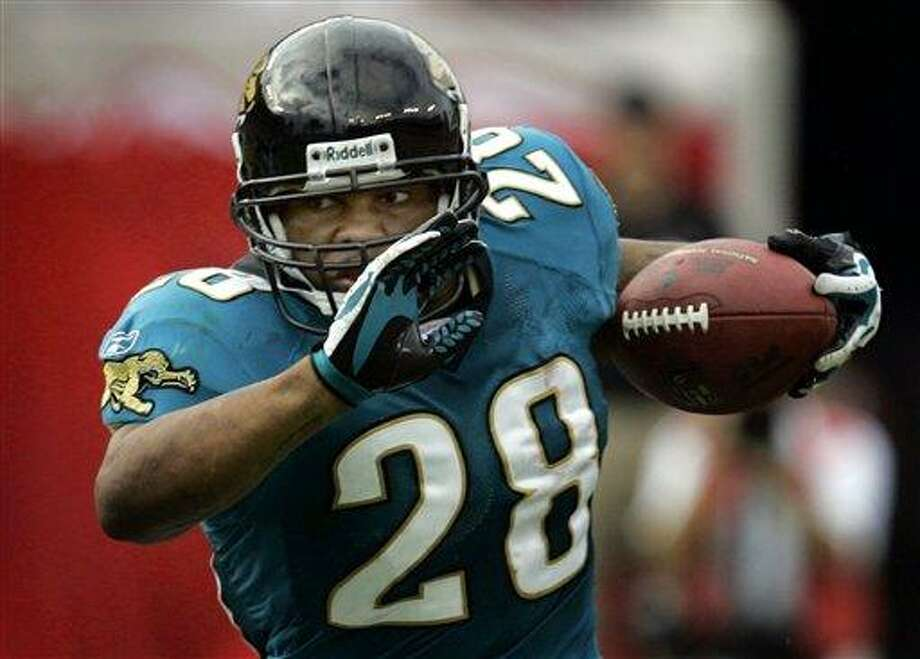 FILE- In this Oct. 28, 2007, file photo, Jacksonville Jaguars running back Fred Taylor carries in the first quarter during an NFL football game against the Tampa Bay Buccaneers in Tampa, Fla. Taylor is retiring from the NFL after 13 seasons and nearly 12,000 yards.  he will sign a one-day contract with the Jaguars on Friday so he can formally retire with the team that drafted him ninth overall in 1998. (AP Photo/Chris O'Meara, File) Photo: AP / 2007 AP