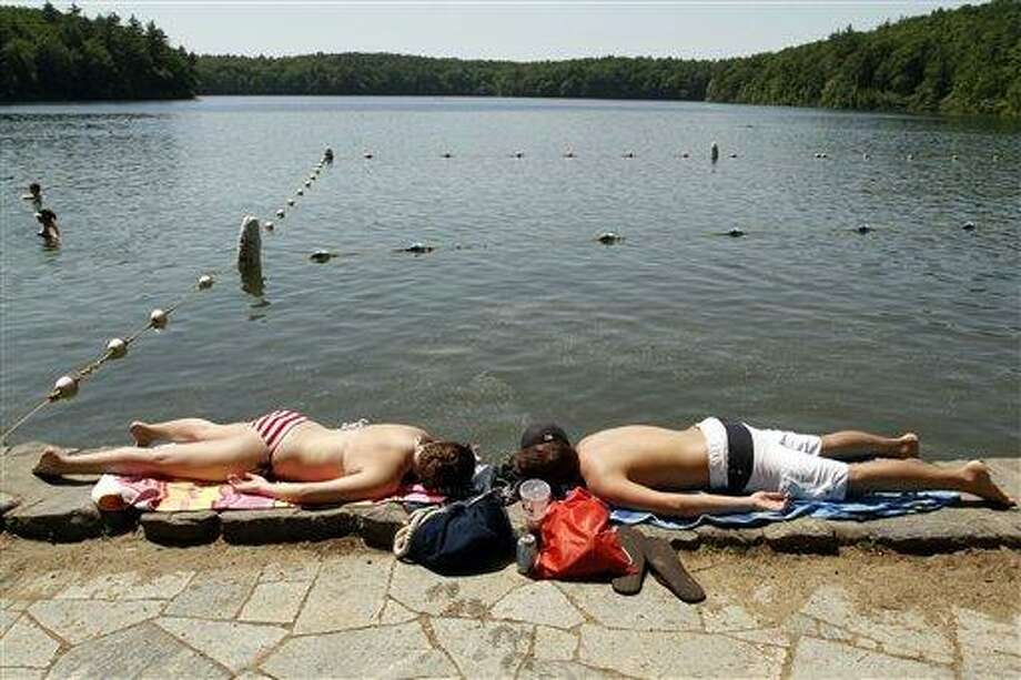 FILE - In this  May, 26, 2010 file photo, Katie Pekkuala, left, and Jake Hebert, right, both of Maynard, Mass., lie on the edge of Walden Pond, in Concord, Mass.  Temperatures soared into the 90s in southern New England to break records for that day of the year. Climatologists at Cornell University said Wednesday, Jan. 5, 2011, that 23 of the 35 cities they monitor in 12 northeastern states had an average temperature in 2010 that ranked among the 10 hottest on record.(AP Photo/Steven Senne, FILE) Photo: AP / AP2010