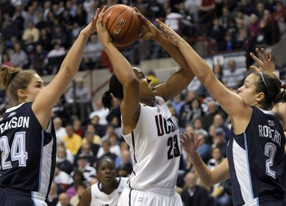 Connecticut's Maya Moore, center, takes a shot as Vilanova's Megan Pearson, left, and Rachel Roberts, right, defend during the first half of an NCAA college basketball game in Storrs, Conn., Wednesday, Jan. 5, 2011. (AP Photo/Bob Child) Photo: AP / FR 170410 AP
