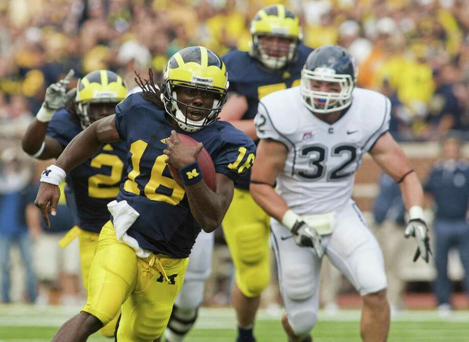 Michigan quarterback Denard Robinson (16) rushes past Connecticut linebacker Scott Lutrus (32) in the first quarter of an NCAA college football game, Saturday, Sept. 4, 2010, in Ann Arbor, Mich. (AP Photo/Tony Ding) Photo: ASSOCIATED PRESS / FR143848 AP